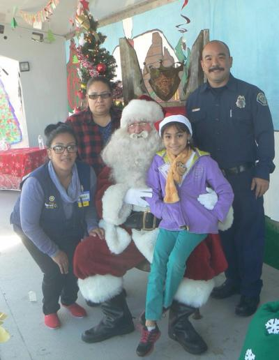 Photo courtesy: CVUSD A student and her family member have their photo taken with Santa, a Chino Police officer, and a Walmart employee at the annual Make A Child Smile event at Walmart in Chino.