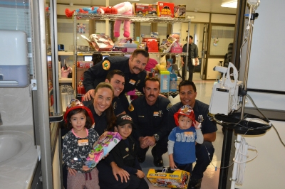 Courtesy of the Chino Valley Fire District (L-R) front row: Child, Public Information Officer Massiel De Guevara, Junior Firefighter Vincent, child receiving care at Children's hospital middle row, Firefighter/Paramedic Shane Stocking, Firefighter Jason Farnsworth, Fire Inspector Alvin Cuna. Far back, Firefighter/Paramedic Tommy Kavanaugh