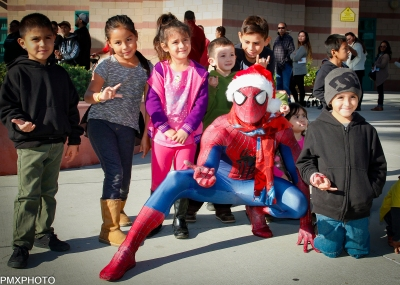 Photo by: Paul Moureaux of pmxphotography.com Spider-Man swings in for the annual Christmas Gift Mart